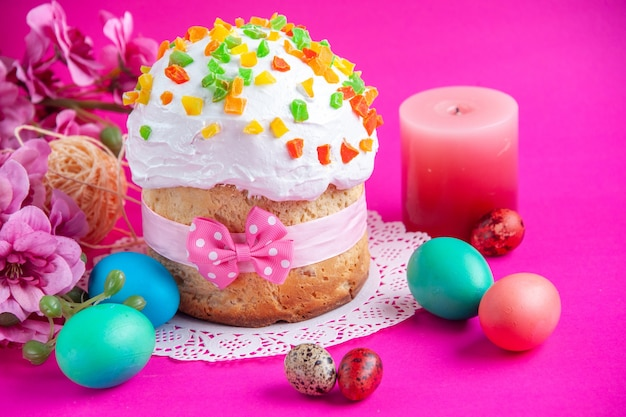 Vista frontale deliziosa torta alla crema con uova colorate e candela su sfondo rosa torta di zucchero torta dolce dessert colorato ornato novruz holiday
