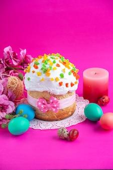 Vista frontale deliziosa torta alla crema con uova colorate e candela su sfondo rosa torta di zucchero torta dolce dessert colorato ornato vacanze di primavera