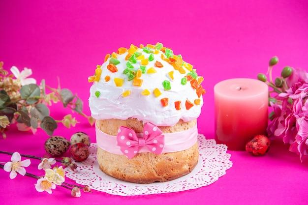 Vista frontale deliziosa torta alla crema con uova colorate e candela su sfondo rosa zucchero colorato ornato novruz dolce primaverile dessert
