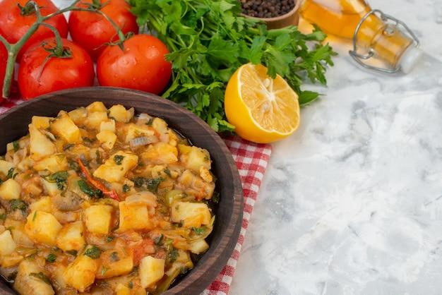 Vista frontale di una deliziosa cena con patate verdi in una ciotola marrone su pomodori tovaglioli spogliati rossi con steli pepe verde fascio caduto bottiglia di olio su sfondo di ghiaccio