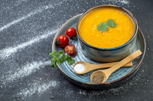 Vista frontale della deliziosa zuppa di lenticchie rosse in una ciotola servita con pomodori verdi pepe sale sul vassoio blu sul lato sinistro su sfondo bianco nero con spazio libero