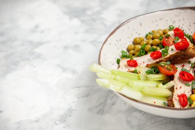 Vista frontale di una deliziosa insalata con vari ingredienti su un piatto sul lato sinistro su una superficie bianca con spazio libero