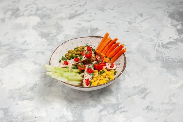 Vista frontale di una deliziosa insalata con vari ingredienti su un piatto su superficie bianca con spazio libero