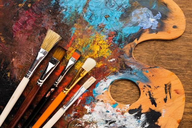 Tavolozza di colori sporchi vista frontale con pennelli