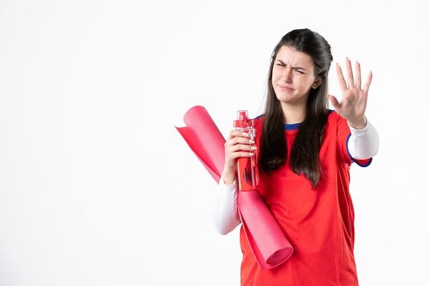 Vista frontale dispiaciuto giovane femmina in abiti sportivi con materassino yoga