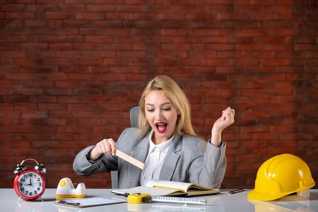 Vista frontale eccitato ingegnere femminile seduto dietro il suo posto di lavoro
