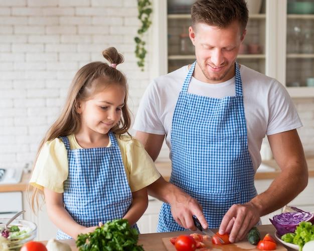 Padre e ragazza di vista frontale che cucinano insieme