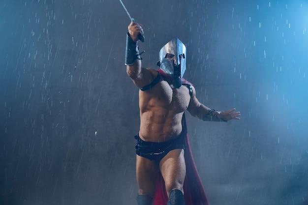 Vista frontale del gladiatore romano bagnato senza paura in elmo di ferro che attacca con la spada. spartano senza camicia urlante muscolare in mantello rosso e armatura in esecuzione durante la lotta in caso di maltempo piovoso.
