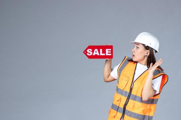 Vista frontale del costruttore femminile che tiene la scheda di vendita rossa sul muro grigio