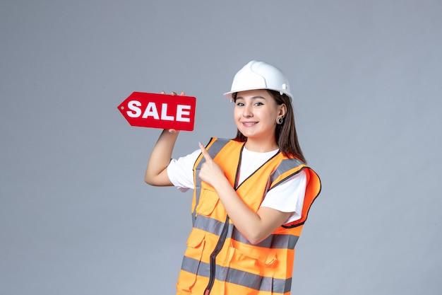 Vista frontale del costruttore femminile che tiene il bordo rosso di vendita sulla parete bianca