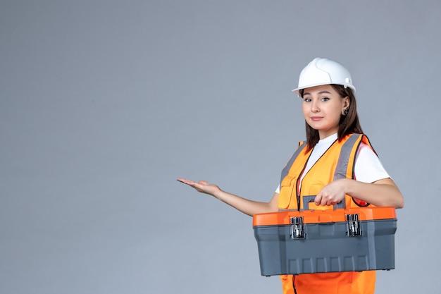 Vista frontale del costruttore femminile che tiene la cassetta degli attrezzi sul muro grigio