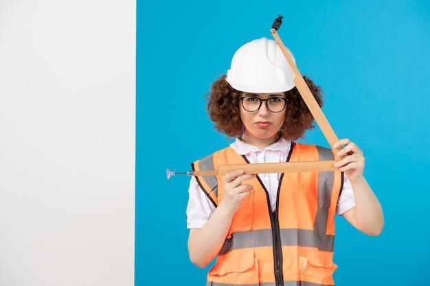 Costruttore femminile di vista frontale in uniforme sull'azzurro