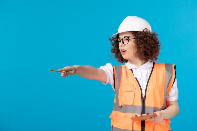 Costruttore femminile di vista frontale in uniforme che controlla il lavoro sull'azzurro