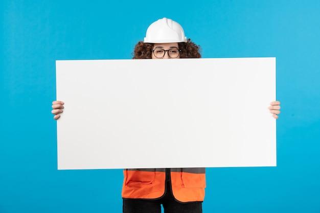 Vista frontale del costruttore femminile in uniforme che tiene lo scrittorio normale bianco sulla parete blu