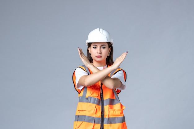 Vista frontale del costruttore femminile in uniforme sul muro bianco