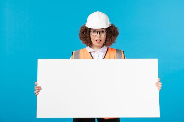 Vista frontale del costruttore femminile in uniforme con parete blu scrivania pianura bianca