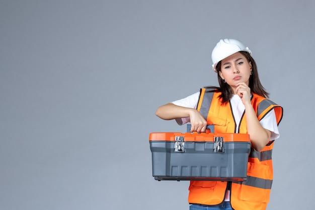 Vista frontale del costruttore femminile con valigetta per attrezzi pesante sul muro grigio