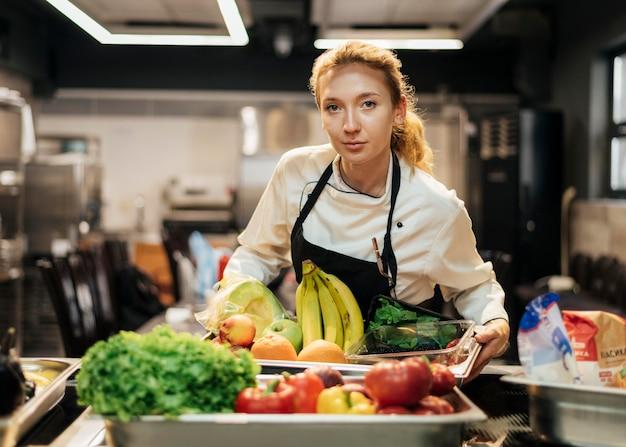 Vista frontale del cuoco unico femminile che tiene vassoio con frutta in cucina