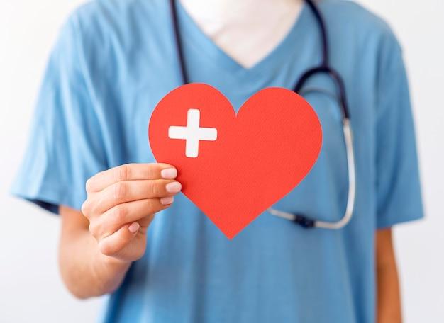 Vista frontale del medico femminile che tiene il cuore di carta