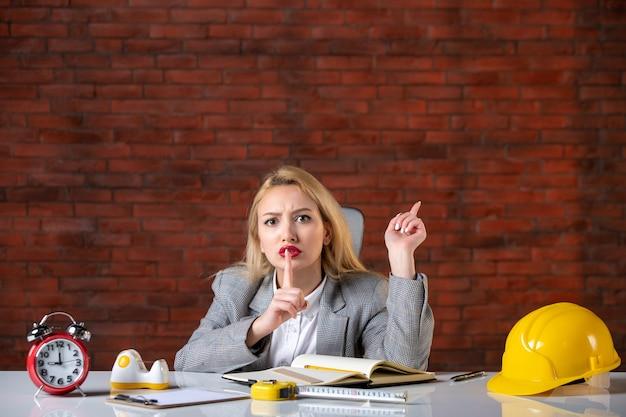 Assistente tecnico femminile di vista frontale che si siede dietro il suo posto di lavoro