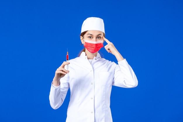 Infermiera femminile di vista frontale in vestito medico bianco con maschera rossa e iniezione nelle sue mani sull'azzurro