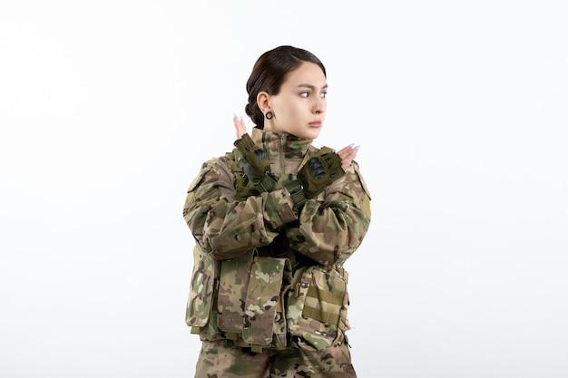Vista frontale della soldatessa in mimetica sul muro bianco