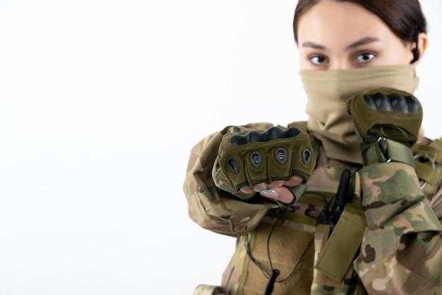 Vista frontale della soldatessa in uniforme militare sul muro bianco