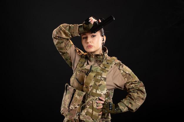 Vista frontale della soldatessa con la pistola in uniforme sul muro nero