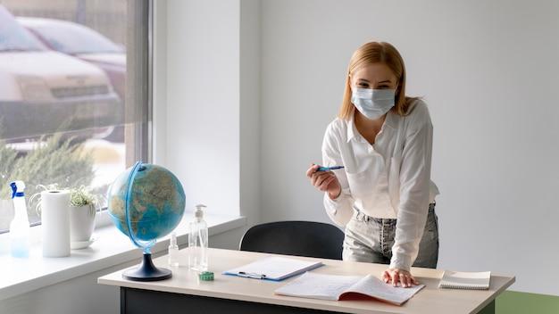 Vista frontale dell'insegnante femminile con mascherina medica allo scrittorio in aula