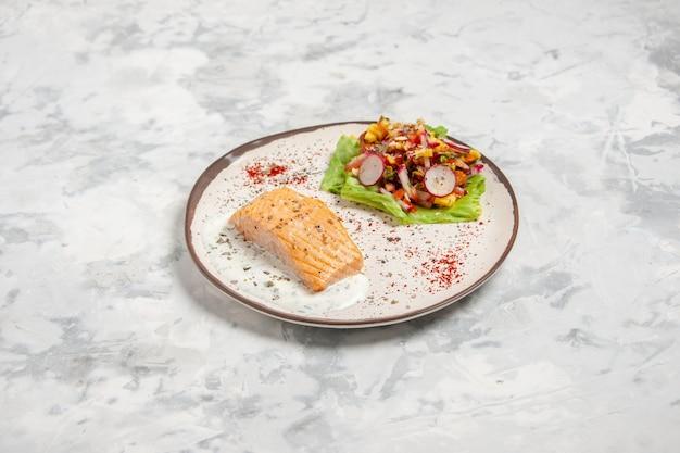 Vista frontale di farina di pesce e deliziosa insalata su un piatto su superficie bianca macchiata con spazio libero free