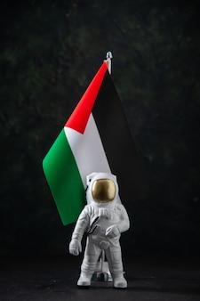 Vista frontale della bandiera della palestina con il giocattolo dell'astronauta sul nero
