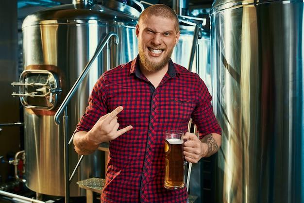 Vista frontale fo pazzo barbuto hipster in piedi nella fabbrica di birra, mantenendo la birra e mostrando il segno del rock. giovane maschio che guarda l'obbiettivo e posa con vetro vicino a macchine per la produzione di birra. concetto di bevanda.