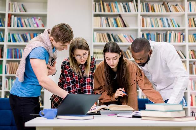 Vista frontale di quattro giovani multietnici concentrati, studenti universitari che si preparano a fare i compiti nella stanza della biblioteca