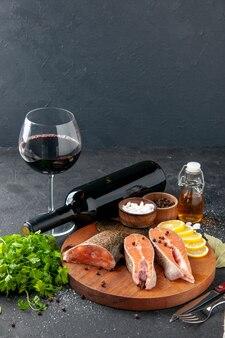 Vista frontale pesce fresco con bottiglia di vino e condimenti sullo sfondo scuro pasto a base di pesce cibo pasto acqua pesce carne insalata oceanica mare