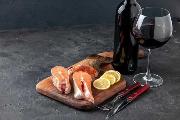 Vista frontale pesce fresco con limone e bottiglia di vino sullo sfondo scuro insalata oceano pasto a base di pesce cibo pasto acqua pesce di mare carne