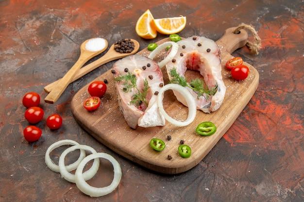 Vista frontale dei pesci crudi freschi e dei pomodori verdi della cipolla del pepe sul tagliere sulla superficie mista di colore