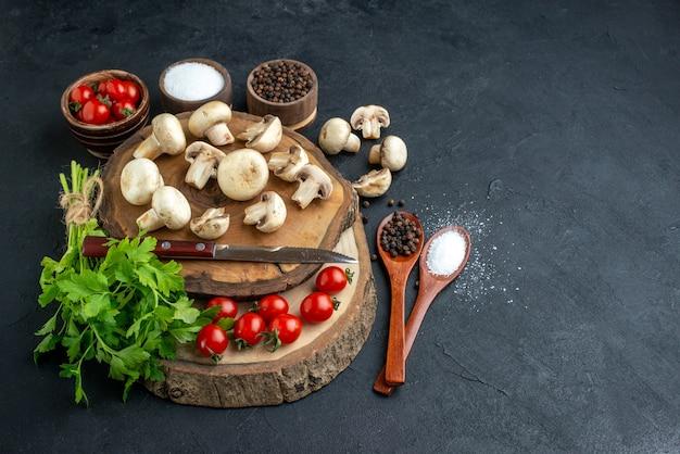 Vista frontale dei funghi crudi freschi e delle spezie verdi dei pomodori del coltello del fascio sull'asciugamano del bordo di legno su fondo nero