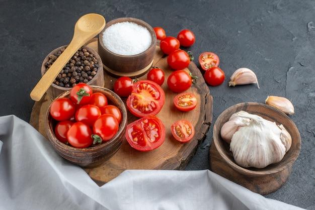Vista frontale di pomodori freschi e spezie su tavola di legno aglio bianco asciugamano su superficie nera