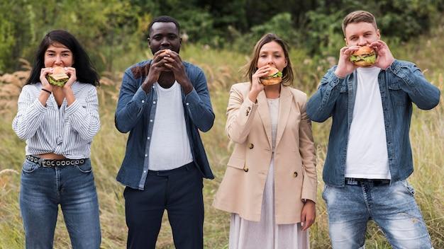 Amici di vista frontale che mangiano hamburger
