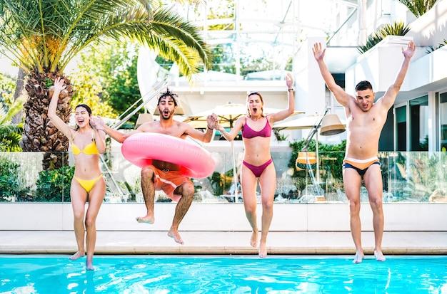 Vista frontale di amici che saltano in piscina con materassino gonfiabile lilo alla festa del resort di lusso