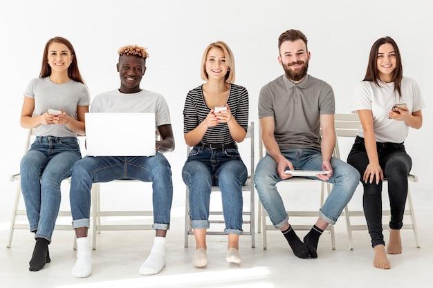 Amici di vista frontale che si siedono sulle sedie con i dispositivi moderni