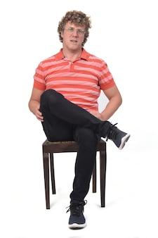 Vista frontale di un ritratto completo di un uomo riccio seduto, gambe incrociate