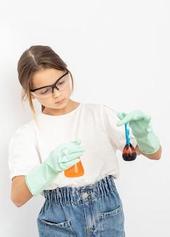 Vista frontale della ragazza che fa esperimenti di chimica