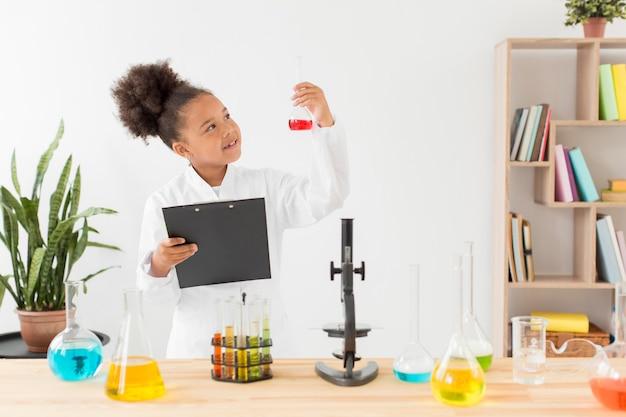 Vista frontale della ragazza in camice da laboratorio guardando la provetta con pozione