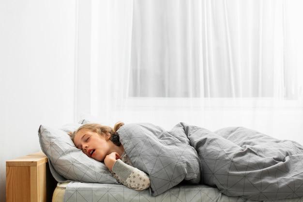 Vista frontale della ragazza che dorme nel letto