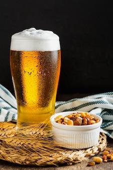 Vista frontale del bicchiere di birra con noci assortite
