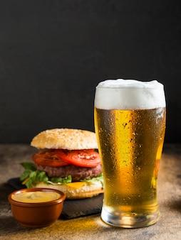 Vista frontale del bicchiere di birra con cheeseburger