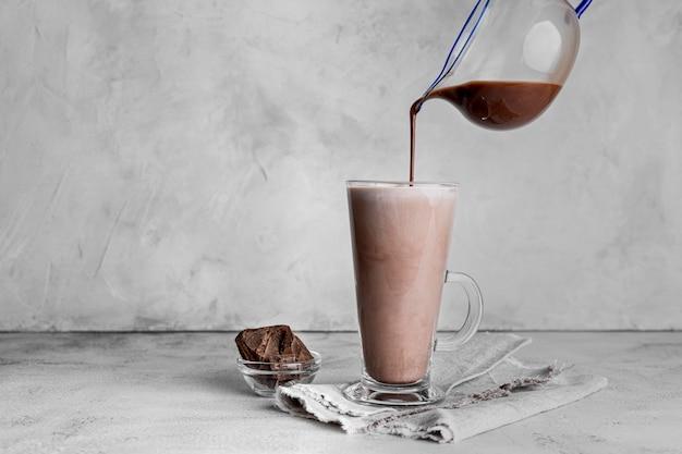 Vista frontale del bicchiere di latte al cioccolato con un panno
