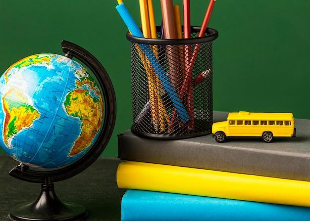 Vista frontale del globo con una pila di libri e scuolabus