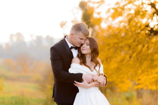 La vista frontale dello sposo abbraccia la bella sposa nel parco autunnale